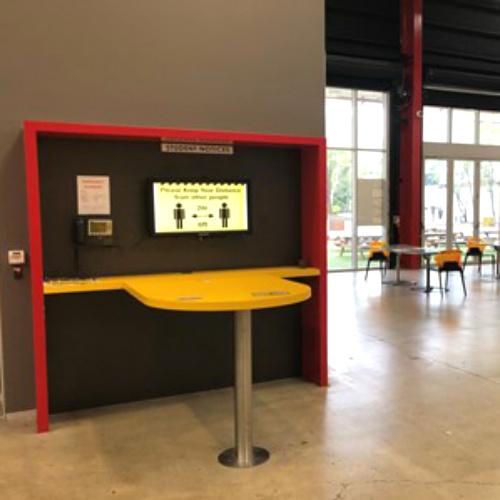 A digital notice board highlighting social distancing measures placed in Café area